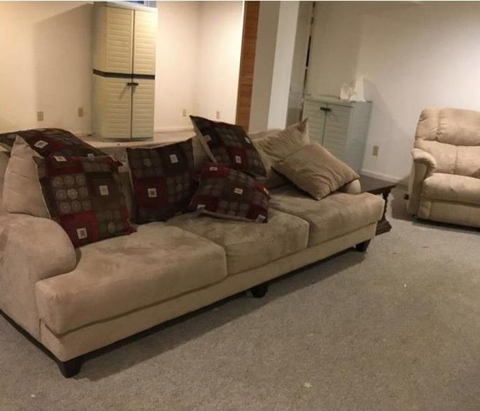 Carpeted basement room with sofa and recliner.
