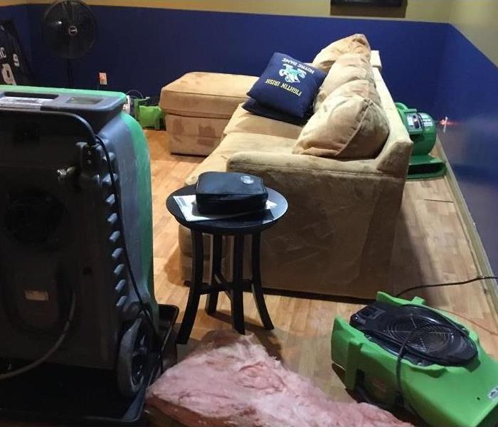 Furnished room with wood flooring and air movers and dehumidifiers set up in the area.