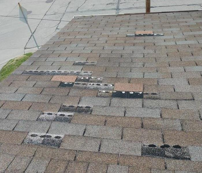 Roof of a building with missing shingles.