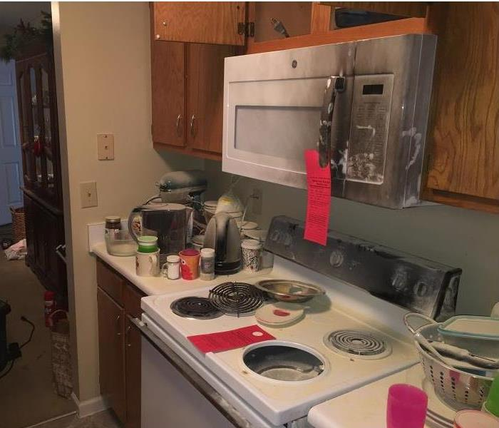 Kitchen in a home showing stove after fire damage. Stove and microwave shows soot and smoke damage.