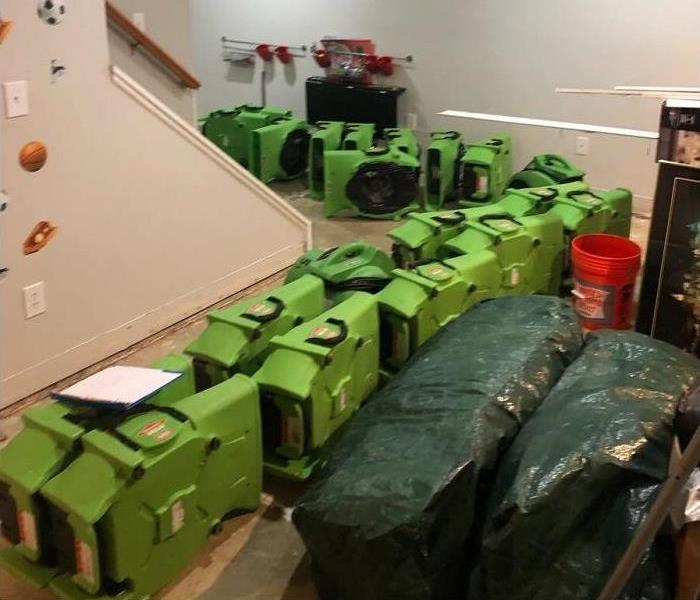 Basement of a home with green air movers lined up.